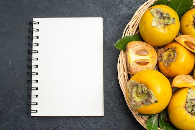 Bovenaanzicht verse zoete kaki in mand op donkere tafel mellow fruit rijp