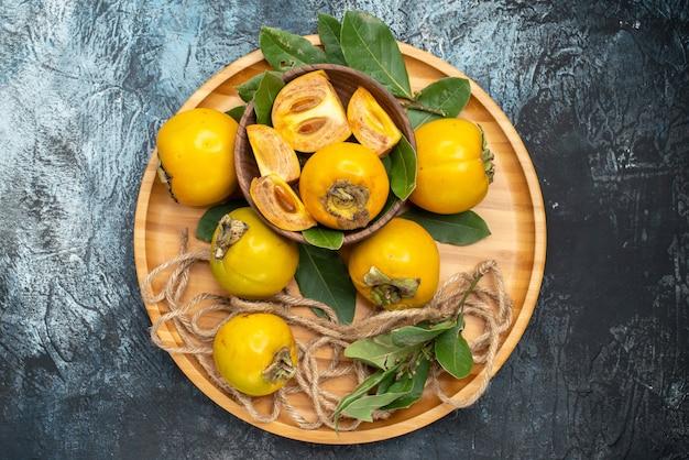 Bovenaanzicht verse zoete kaki op de donkere tafel rijp fruit