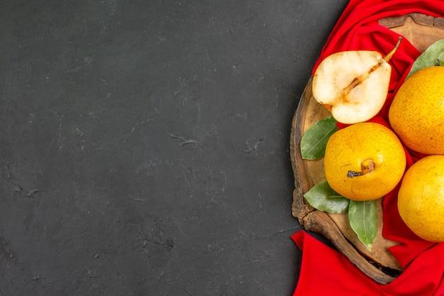 Bovenaanzicht verse zoete peren op rood weefsel en donkere tafel rijpe frisse kleur mellow
