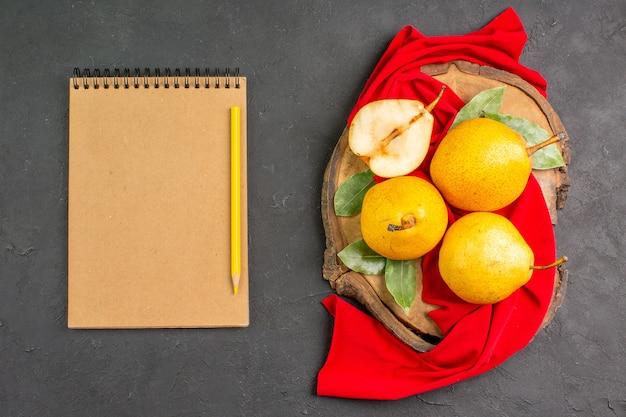 Bovenaanzicht verse zoete peren op rood weefsel en donkere vloer rijpe frisse kleur mellow