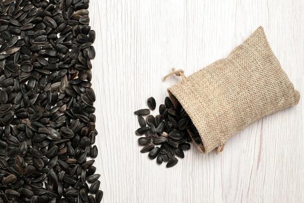 Bovenaanzicht verse zonnebloempitten zwart gekleurde zaden op wit oppervlak zaad likdoorns snack foto veel olie Gratis Foto