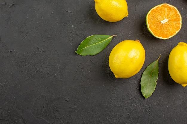 Bovenaanzicht verse zure citroenen bekleed op donkere tafel, citrus limoen geel fruit