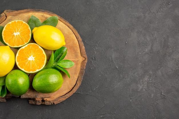 Bovenaanzicht verse zure citroenen op de donkere tafel fruit citrus limoen Gratis Foto