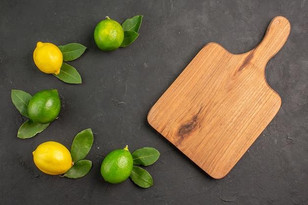 Bovenaanzicht verse zure citroenen op de donkere tafel fruit limoen citrus