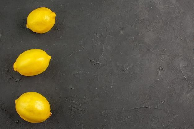 Bovenaanzicht verse zure citroenen op de donkere tafel limoen citrus geel fruit