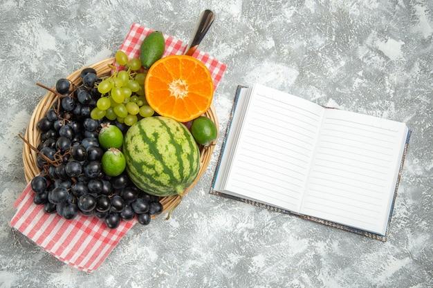 Bovenaanzicht verse zwarte druiven met sinaasappel en feijoa op wit oppervlak rijp fruit, zachte vitamineboom vers