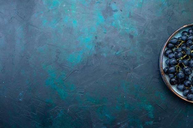 Bovenaanzicht verse zwarte druiven op donkerblauw