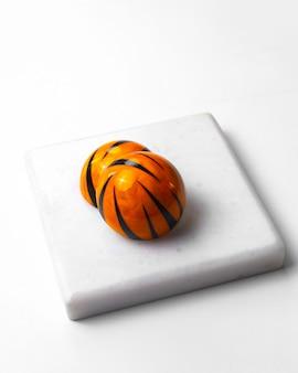 Bovenaanzicht versierd tijger kleurende chocolade snoep op witte standaard