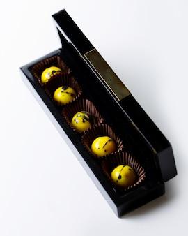Bovenaanzicht versierde gele gespikkelde chocoladesuikergoed in een zwarte gouden doos