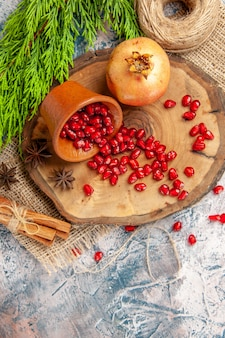 Bovenaanzicht verspreide granaatappelzaden in kom op boom houten bord stro draad kaneel anijs zaden op blauw-witte achtergrond