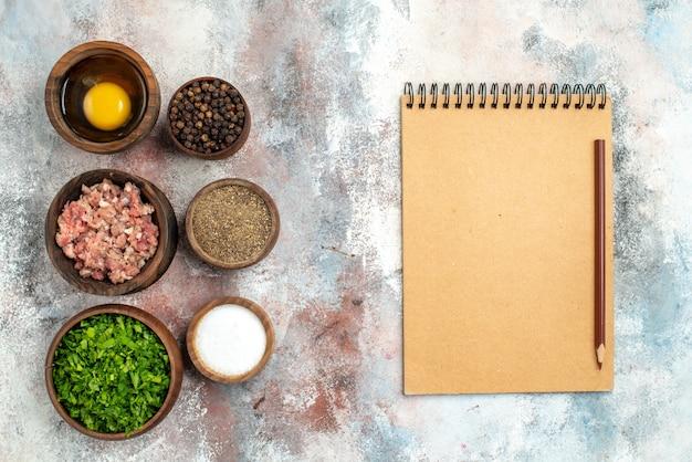 Bovenaanzicht verticale rij kommen met vlees greens eigeel peper poeder zwarte peper zout een notitieboekje op naakt oppervlak