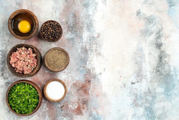 Bovenaanzicht verticale rij kommen met vlees greens eigeel peper poeder zwarte peper zout op naakt oppervlak vrije ruimte