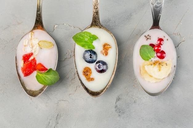 Bovenaanzicht verzameling lepels met yoghurt en fruit