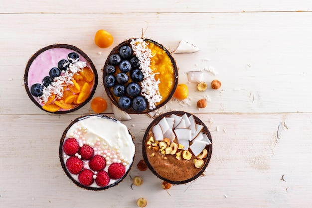 Bovenaanzicht vier kleurrijke smoothie-kommen met bevroren banaan, bosbessen, frambozen, physalis en kokosschaafsel in kokoskommen op witte achtergrond