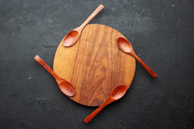 Bovenaanzicht vier lepels op ronde bord op donkere tafel met kopie ruimte