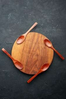 Bovenaanzicht vier lepels op ronde bord op donkere tafel