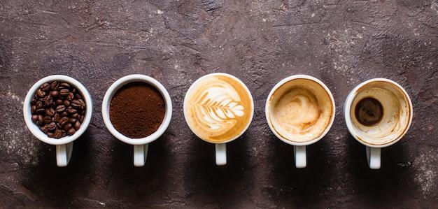 Bovenaanzicht vijf kopjes van verschillende stadia van het bereiden van cappuccino met kopieerruimte