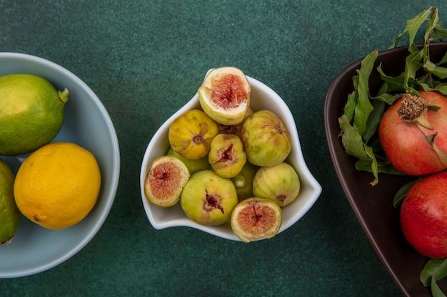 Bovenaanzicht vijgen in een kom met citroenen en granaatappels op een groene achtergrond