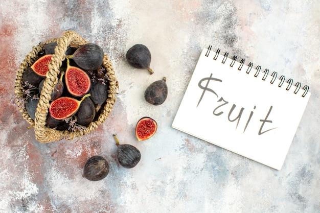 Bovenaanzicht vijgenmand vijgen fruit geschreven op notebook op grijze achtergrond