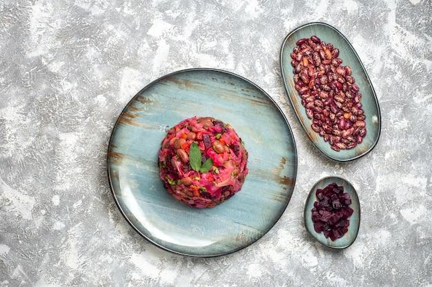 Bovenaanzicht vinaigrette bietenaardappelsalade op ronde bordbonen en gesneden biet op borden op lichttafel