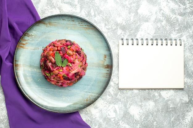 Bovenaanzicht vinaigrette bietenaardappelsalade op ronde plaat paarse sjaal notebook op lichttafel