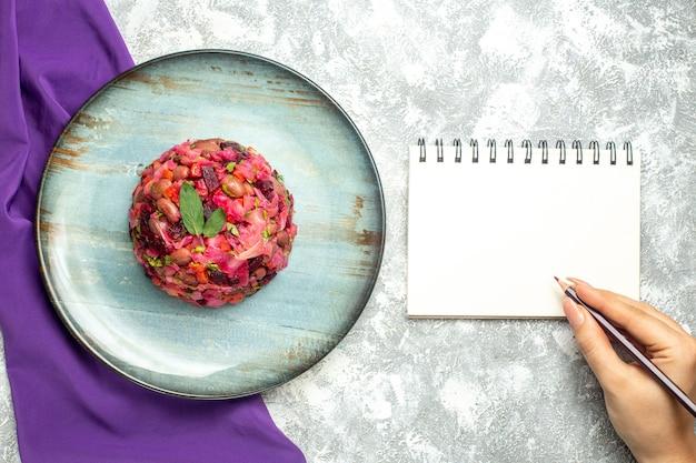 Bovenaanzicht vinaigrette bietenaardappelsalade op ronde plaat paarse sjaal notitieblok potlood in vrouwelijke hand op lichttafel