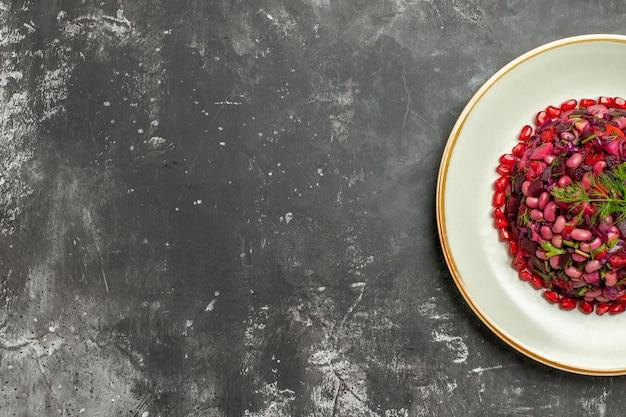 Bovenaanzicht vinaigrette salade met granaatappels en bonen op donkere ondergrond