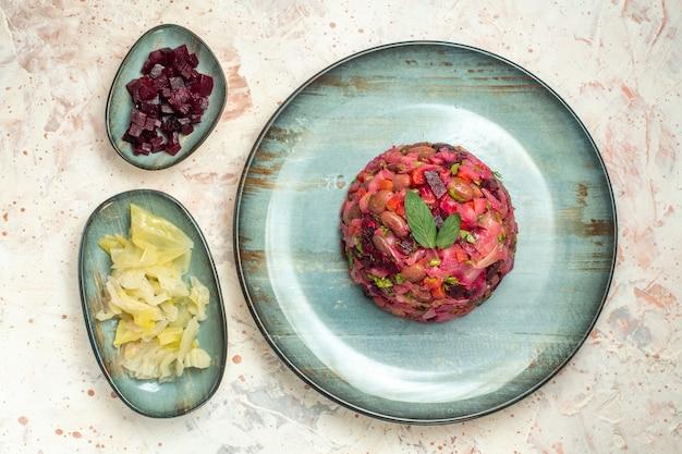 Bovenaanzicht vinaigrette salade op ovale plaat gesneden biet en andere dingen in kommen op lichtgrijze tafel