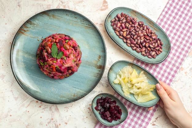 Bovenaanzicht vinaigrette salade op plaat zuurkool bonen gesneden bieten op borden zuurkool in vrouwelijke hand op lichtgrijze tafel