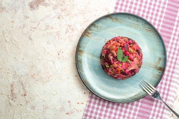 Bovenaanzicht vinaigrette saladevork op ovale plaat op wit en paars geruit tafelkleed op lichtgrijze tafelkopieerplaats