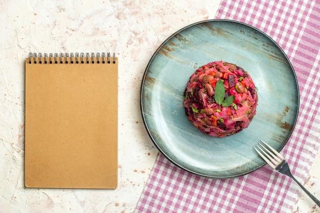 Bovenaanzicht vinaigrette saladevork op ovale plaat op wit en paars geruit tafelkleednotitieboekje op lichtgrijze tafel