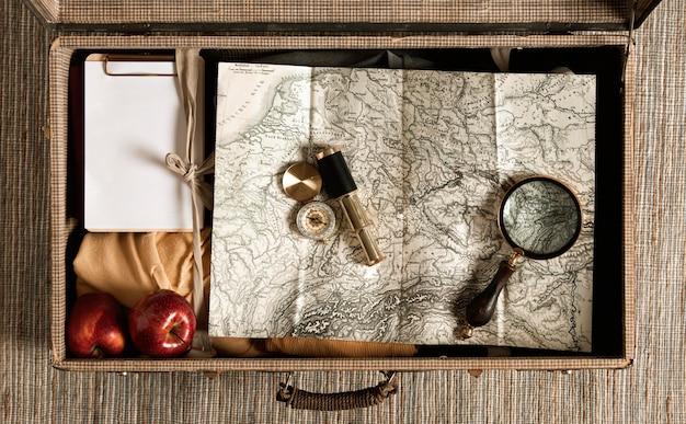 Bovenaanzicht vintage koffer met kaart en vergrootglas