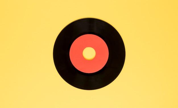 Bovenaanzicht vinyl schijf op gele achtergrond