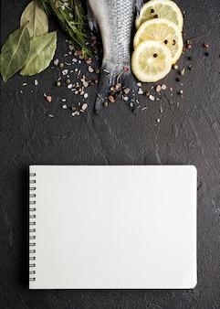 Bovenaanzicht vis met kruiden en notitieboekje