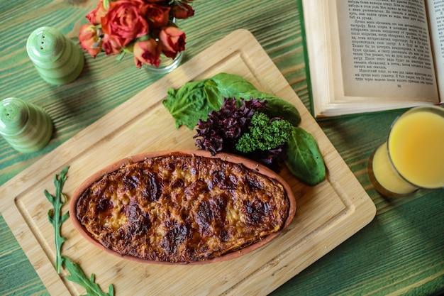Bovenaanzicht vlees braadpan met kruiden op een stand met sinaasappelsap op tafel