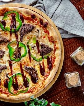 Bovenaanzicht vlees pizza met paprika en barbecue saus op een dienblad