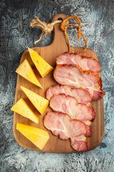 Bovenaanzicht vlees plakjes kaas plakjes op snijplank op grijze ondergrond