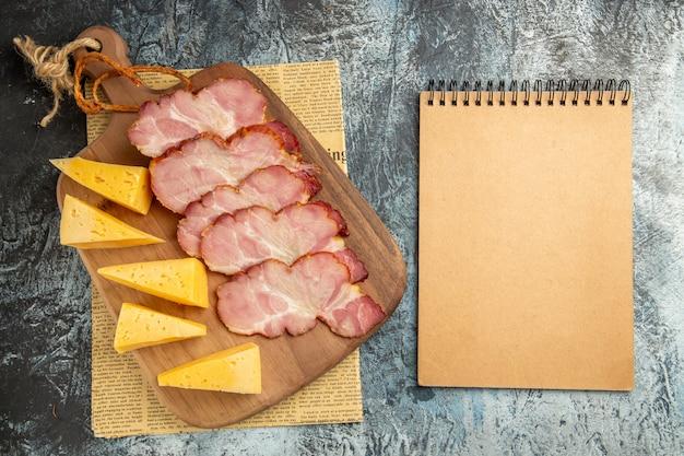 Bovenaanzicht vlees plakjes kaas plakjes op snijplank op krant notitieblok op grijs oppervlak