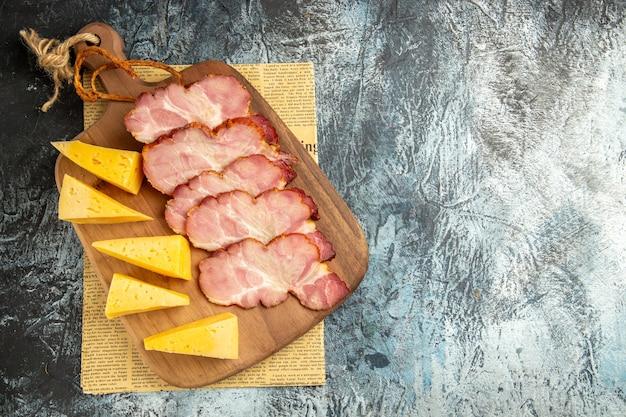 Bovenaanzicht vlees plakjes kaas plakjes op snijplank op krant op grijze ondergrond