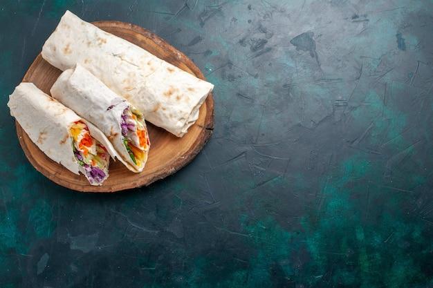 Bovenaanzicht vlees sandwich een sandwich gemaakt van vlees gegrild aan het spit met groenten op donkerblauw bureau sandwich hamburger eten maaltijd lunch