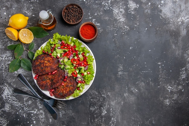 Bovenaanzicht vleeskoteletten met salade en brood