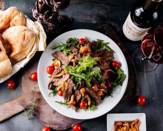 Bovenaanzicht vleesmaaltijd samen met groenten in witte plaat op het bruine bureau en donkere oppervlak