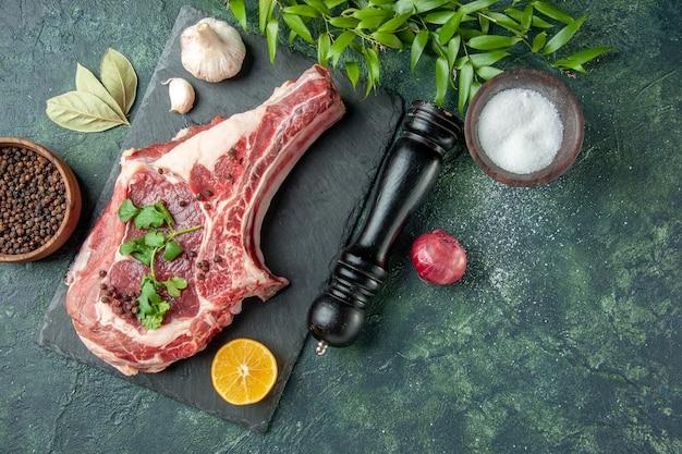 Bovenaanzicht vleesplak met peper en zout op donkerblauwe achtergrondkleur voedsel vlees keuken dier kip koe slager
