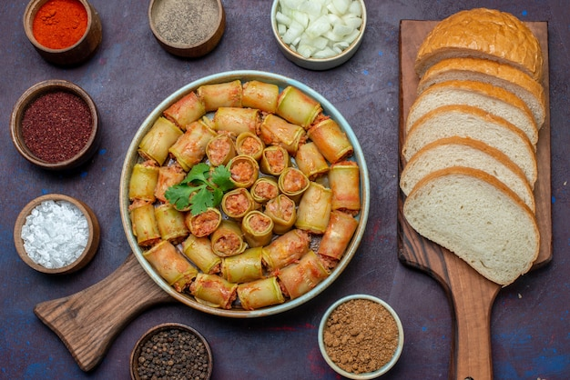 Bovenaanzicht vleesrolletjes gerold in pompoenen in de pan samen met kruiden en brood op donker bureau vlees plantaardig voedsel diner
