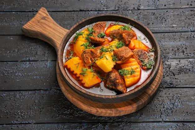 Bovenaanzicht vleessaus soep met aardappelen en greens op donkere vloer
