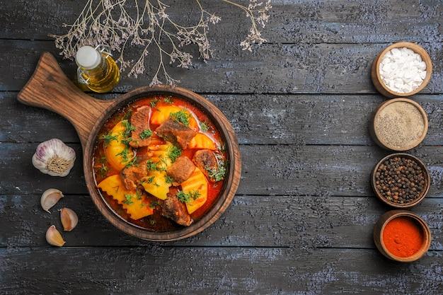 Bovenaanzicht vleessaus soep met greens en aardappelen op het donkere bureau