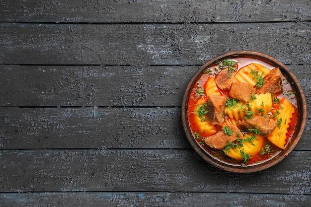 Bovenaanzicht vleessoep met aardappelen en greens op de donkere vloer
