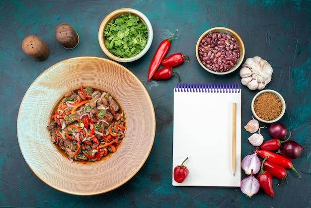Bovenaanzicht vlezige groentemaaltijd in plaat samen met groene paprika's bonen groenten met blocnote op het donkerblauwe bureau voedselmaaltijd groentekruiden