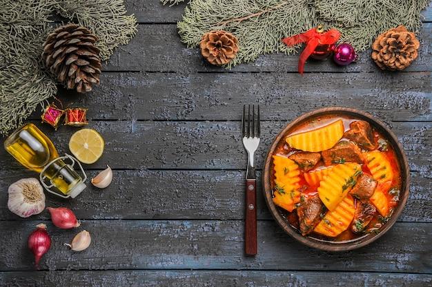 Bovenaanzicht vlezige soep met aardappelen en groenten op het donkere bureau