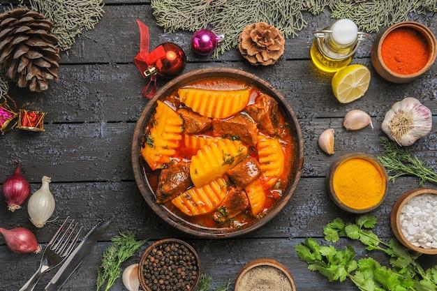 Bovenaanzicht vlezige soep met greens en aardappelen op donkere vloer